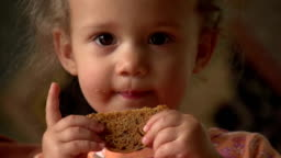 Cute little girl eating a cookie, close up