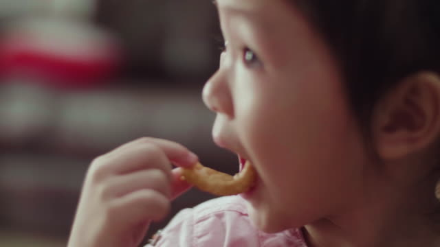 cu : cute little girl eating a cookie - snack stock videos & royalty-free footage