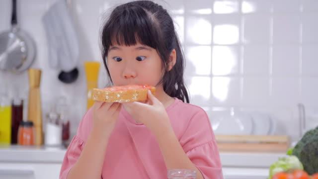 かわいい女の子彼女はトーストとジャムの朝食を食べるします。日本の家族 - 朝食点の映像素材/bロール