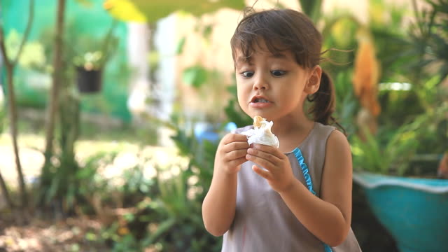 Cute little girl eating ice cream cone.