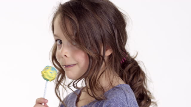 vídeos y material grabado en eventos de stock de cute little girl (seven-years-old) eats a cake pop - fondo blanco