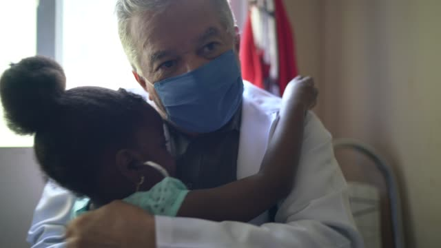 cute little girl examining doctor listening to heartbeat - visit stock videos & royalty-free footage