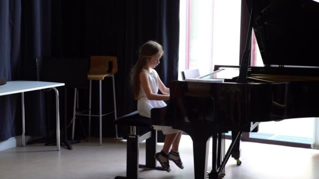 cute little girl grand playing piano, bach - pianist stock-videos und b-roll-filmmaterial