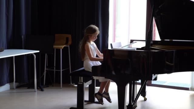 Cute little girl grand playing piano, Bach