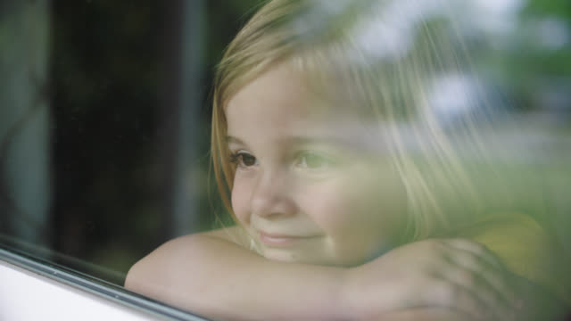 slo mo. cu of cute little girl grinning while looking out window - only girls stock videos & royalty-free footage