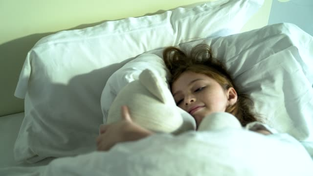 a cute little girl has a good dreaming with a teddy bear in bed. - pillow stock videos and b-roll footage