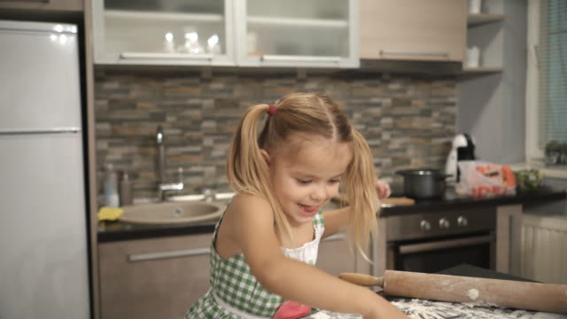 Cute little girl having fun with raw dough and making round shapes with drinking glass.