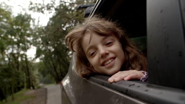 vidéos et rushes de hd: mignonne petite fille en voiture. - regarder par la fenêtre