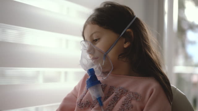 cute little girl inhaling through respiratory machine at home, 4k video - respiratory machine stock videos & royalty-free footage