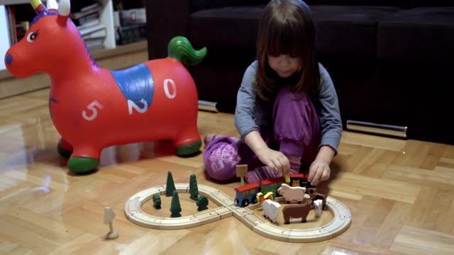 かわいい女の子が木製の列車セットで遊んでいる - railway track点の映像素材/bロール