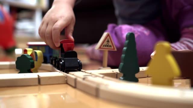 söt liten flicka leker med trä tåg set - leksak bildbanksvideor och videomaterial från bakom kulisserna