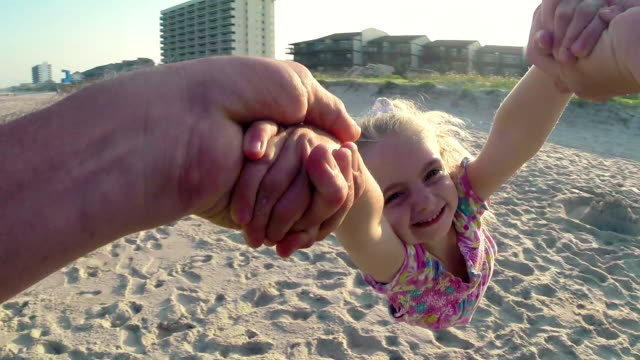 cute little girl laughs as dad swings her around on sunny beach - drehen stock-videos und b-roll-filmmaterial