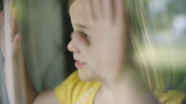 slo mo. cu of cute little girl looking out a window. - only girls stock videos & royalty-free footage