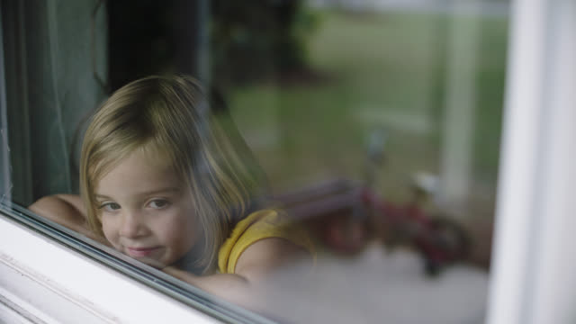 slo mo. cu of cute little girl looking out window. - window点の映像素材/bロール