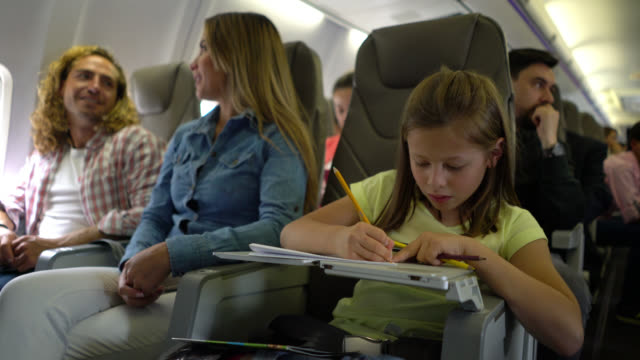 cute little girl looking very focused coloring while other people talk during a commercial flight - passenger stock videos & royalty-free footage