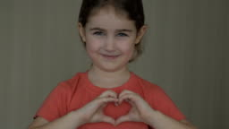 Cute little girl making a heart with her hands and smiling. Young beautiful girl smiling in love showing heart symbol and shape with hands. Romantic concept. Mothers Day.
