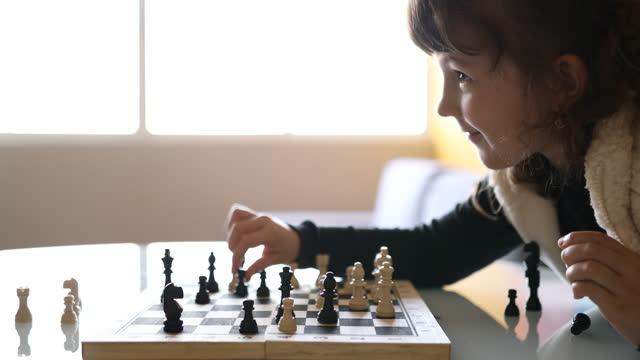 チェスゲームで彼女の次の動きを作るかわいい少女 - dia点の映像素材/bロール
