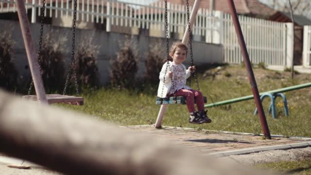 vídeos y material grabado en eventos de stock de linda niña en un columpio en el patio de recreo stock video - columpiarse