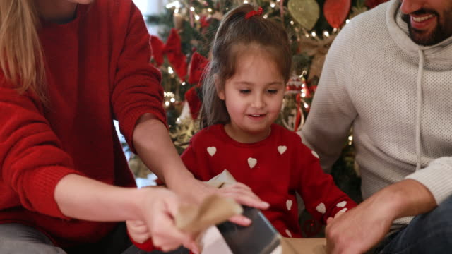 cute little girl opening christmas gifts with her parents - christmas present stock videos & royalty-free footage