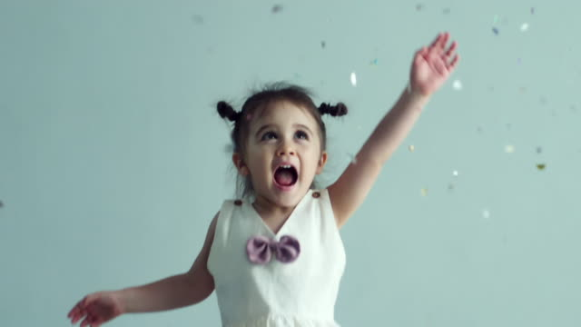 cute little girl(2-3 years) playing and enjoying colorful confetti - baby girls stock videos & royalty-free footage