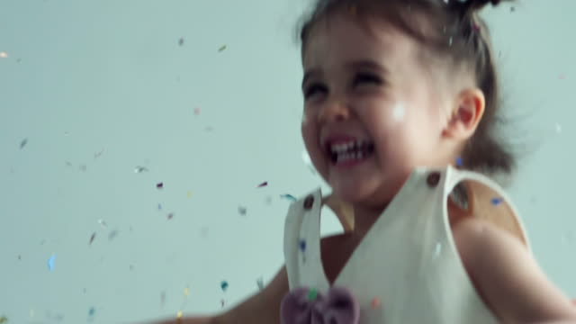 cute little girl(2-3 years) playing and enjoying colorful confetti - 2 3 years stock videos & royalty-free footage
