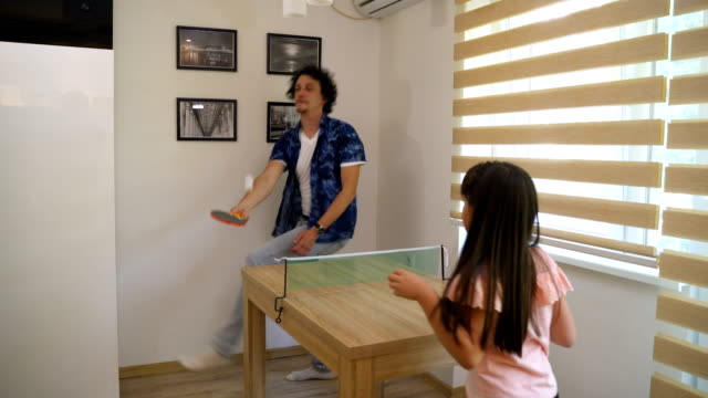 cute little girl playing table tennis at home with her father - table tennis stock videos & royalty-free footage