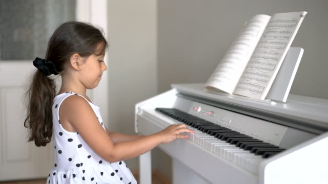 Cute little girl playing the piano