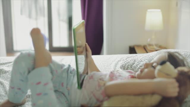 vídeos y material grabado en eventos de stock de niña linda relajarse en casa con tecnología - cómodo conceptos
