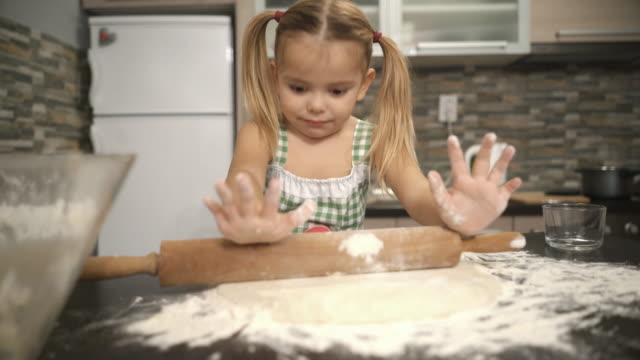 Cute little girl rolling raw dough in the kitchen.