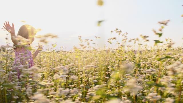 SLO MO Cute little girl running in the buckwheat field