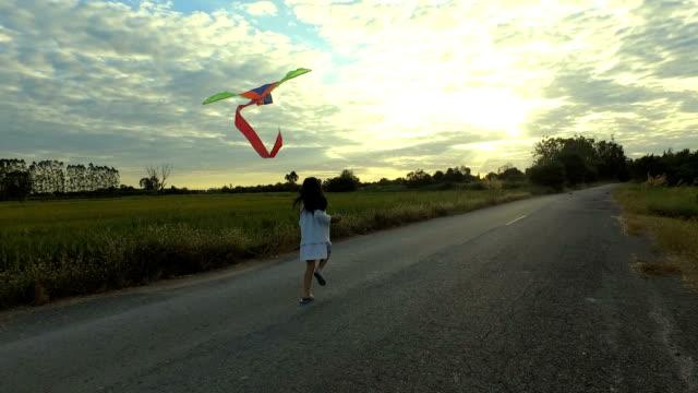 en söt liten flicka kör mot kameran med en drake. solnedgång - kite toy bildbanksvideor och videomaterial från bakom kulisserna