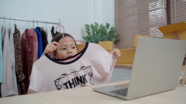 nettes kleines mädchen verkaufen tuch online mit laptop im wohnzimmer in der wohnung - little girl webcam stock-videos und b-roll-filmmaterial