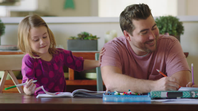 ms. cute little girl shakes dad for attention to show off her magic marker drawing and dad gives her a proud high five. - homework stock videos & royalty-free footage