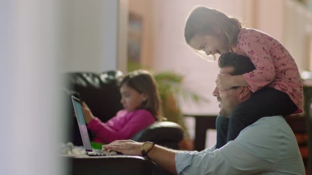 ms. cute little girl sits on dad's shoulders and covers his eyes as he tries to work on laptop in family living room. - familie stock-videos und b-roll-filmmaterial