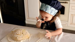 Cute little girl smeared with flour licks her fingers with dough in the kitchen.