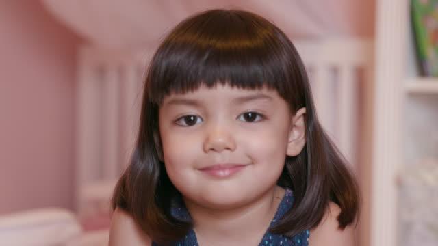 vídeos de stock, filmes e b-roll de cute little girl (3-4) smiling and looking at camera - foto de cabeça