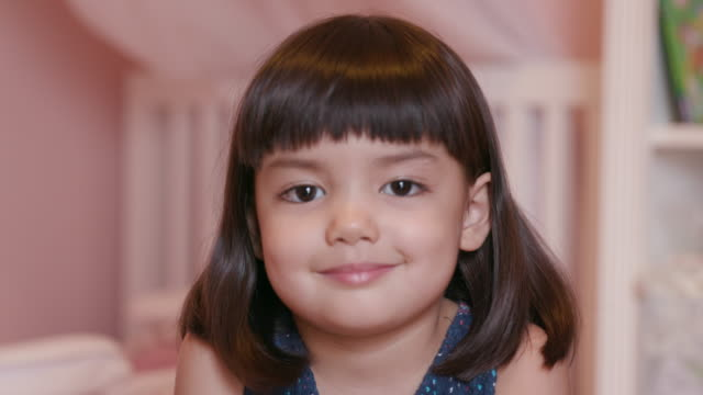 vídeos de stock, filmes e b-roll de cute little girl (3-4) smiling and looking at camera - cabeça