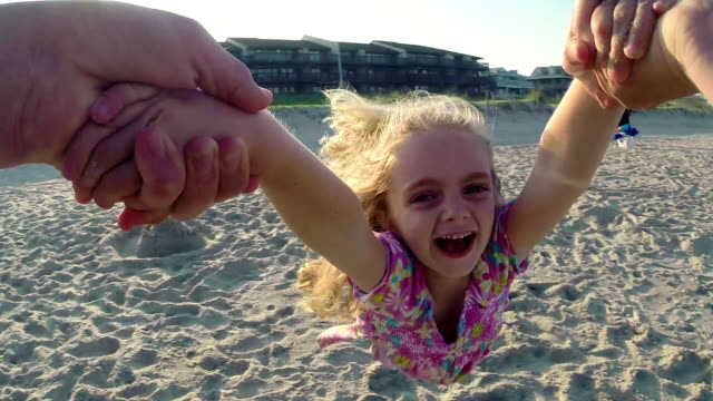 Cute little girl spins in father's arms on sunny beach