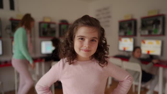 現代のコンピュータスクールの教室に立っているかわいい女の子 - 座る点の映像素材/bロール