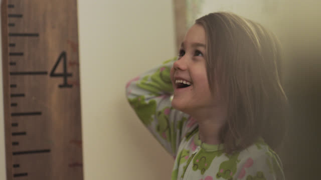 CU. Cute little girl stands up straight and smiles as dad measures her height against the wall before bedtime.