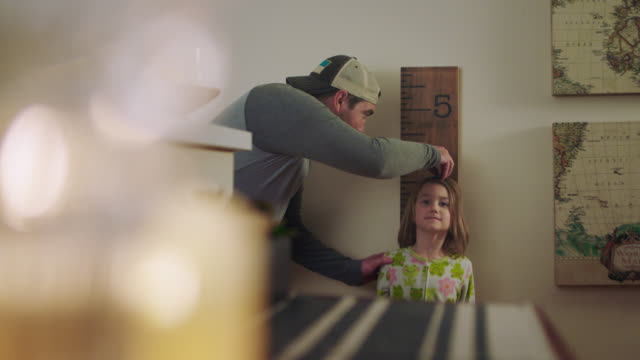 WS. Cute little girl stands up straight and smiles as dad measures her height against the bedroom wall and gives her goodnight kiss.