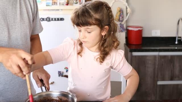彼女の父親が彼女を導いている間、鍋をかき混ぜるかわいい女の子 - dia点の映像素材/bロール