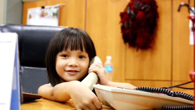 A cute little girl talking on the phone
