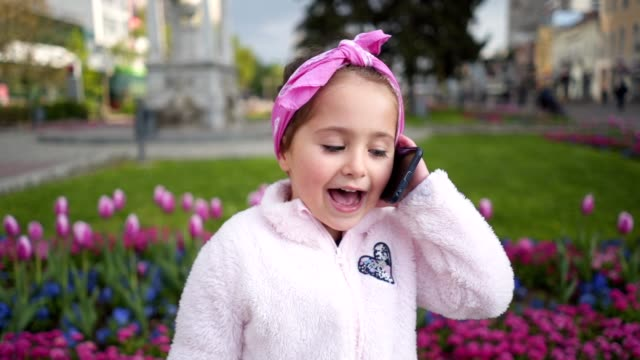 cute little girl talking to her best friend via mobile phone on a lovely spring day - girl sitting cross legged stock videos & royalty-free footage