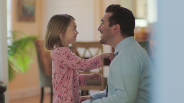 vídeos y material grabado en eventos de stock de ms. cute little girl tightens dad's tie with a grin before he leaves for work in morning. - bien vestido