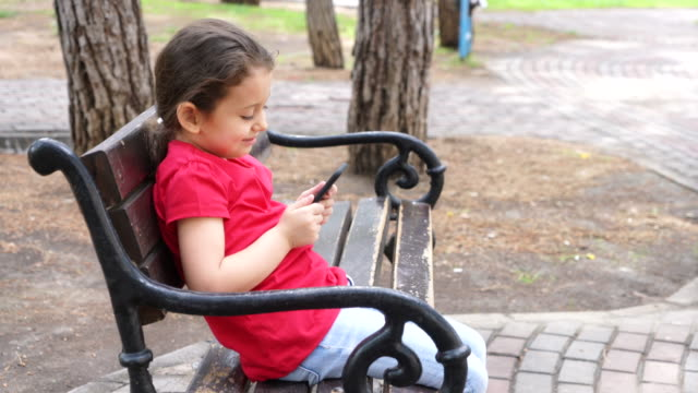 cute little girl using mobile phone - ozgurdonmaz stock videos and b-roll footage