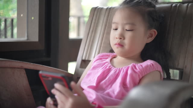cute little girl using smartphone relax on the bench - digital native stock videos & royalty-free footage