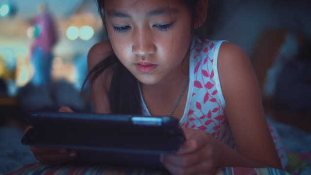 Mignonne petite fille à l'aide de tablette dans la nuit, Close-up