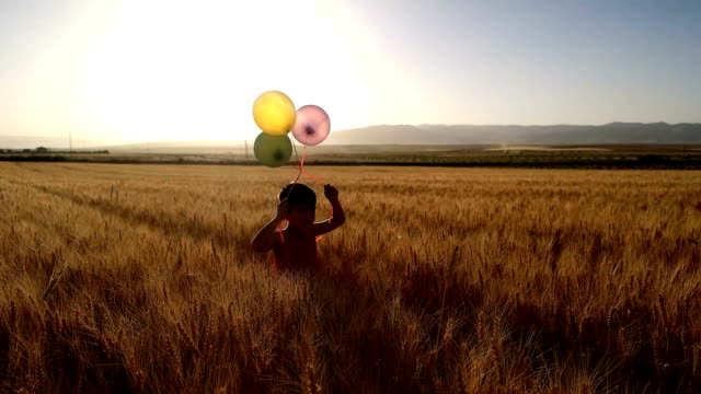 SLOW MOT Cute little girl with balloons at field