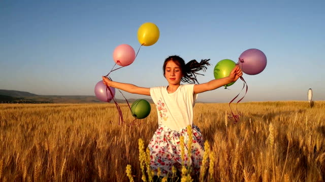 slow-mot cute little girl with balloons at field - turchia video stock e b–roll
